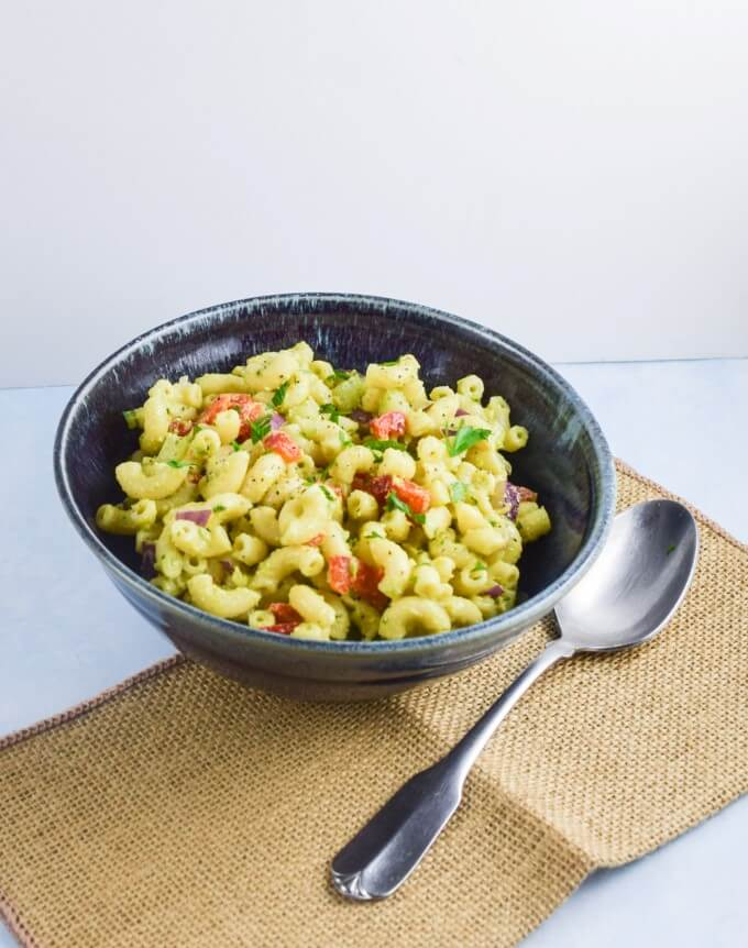 Avocado and lemon make a light dressing for a nutrient dense vegan, nut and soy free, macaroni salad with fresh vegetables and a parsley garnish