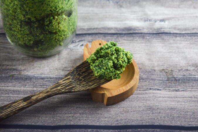 One wooden reusable fork filled with vegan kale, garlic scape, and walnut pesto perfect for a summer pasta!