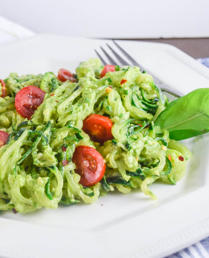Closeup of avocado pesto zucchini noodles with classic garlic, basil, and olive oil for Italian flavor, brought to life with umami miso and served with fresh grape tomatoes