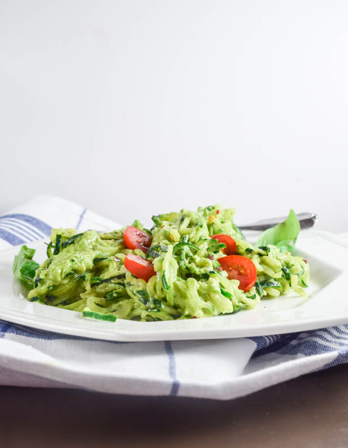 Luscious pesto inspired avocado and lemon juice sauce served over fresh cold zucchini noodles with juicy cherry tomatoes on a white plate