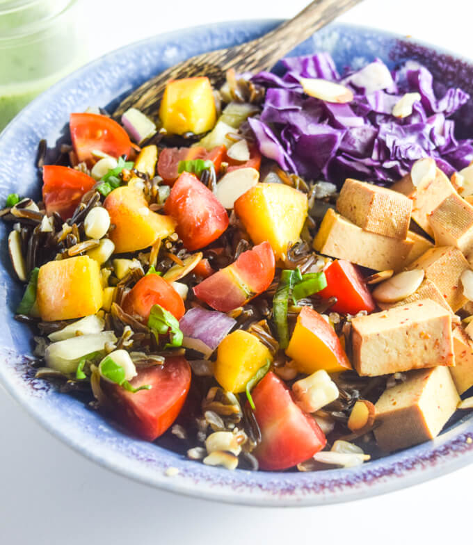 Closeup of a blue bowl of smoked tofu, purple cabbage, red cherry tomatoes, sweet peach, and crunchy slivered almonds, served over chewy wild rice