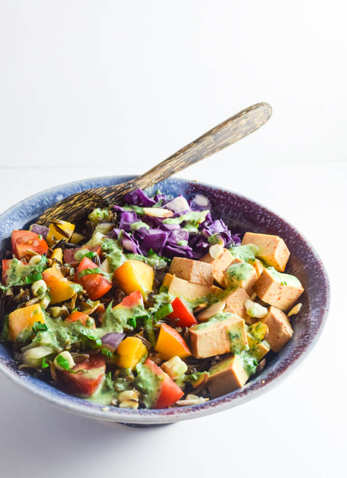 A fresh summer salad with sweet nectarine, smoky tofu, crunchy purple cabbage, and a fresh creamy cashew garlic and basil vinaigrette served in a blue bowl with a wooden spoon