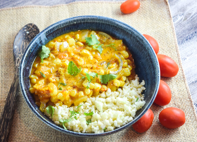 Chunky and filling sweet corn curry filled with nutrient dense fresh vegetables mingled with warm spices and finished with coconut milk and served with light cauliflower rice with a side of cherry tomatoes