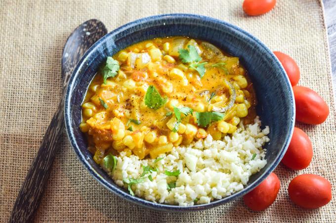 A blue bowl of hearty Indian inspired sweet corn curry spiced with fenugreek, ancho chili powder, garam masala, and turmeric for a flavorful satisfying meal