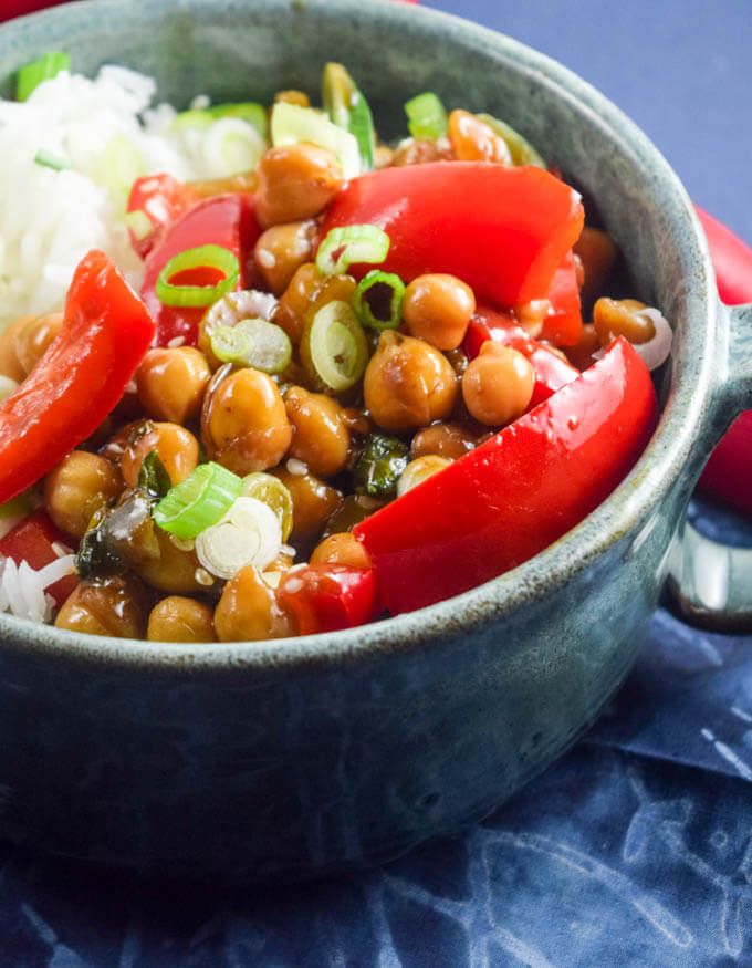 Crunchy red bell peppers and chickpeas coated in a homemade kung pao sauce with balsamic vinegar, agave, and sriracha, garnished with green onions and served over hot white rice in a blue bowl | Yup, it's Vegan