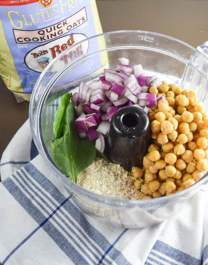 Falafel ingredients in a food processor - chickpeas, red onion, gluten free quick cooking oats, and spinach greens