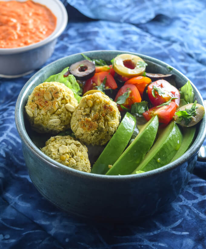 Fresh vegan baked falafel bowl with from scratch falafel, creamy avocado, salty kalamata olives, juicy red tomatoes, and fresh mixed greens with a parsley garnish