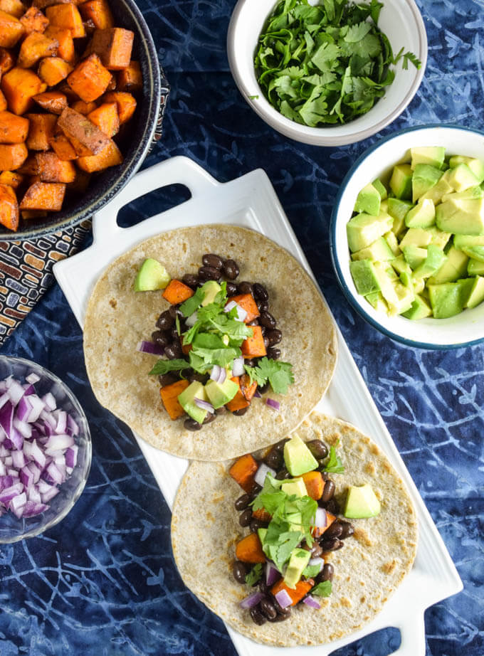 Healthy and comforting, gluten free and vegan tacos, sticky bbq sauce coated roasted sweet potatoes, spiced black beans, rich avocado, and fresh herbs with lime juice