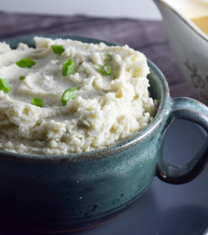 Close up of a blue mug of super simple three ingredient ultra creamy garlic roasted mashed potatoes garnished with scallions