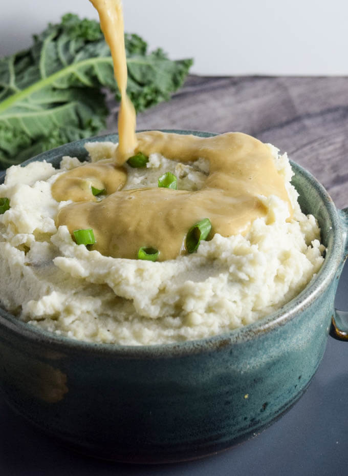 Bowl of extra creamy garlic roasted mashed russet potatoes with a white bean gravy made with miso and nutritional yeast, spiced with thyme and miso for the perfect texture