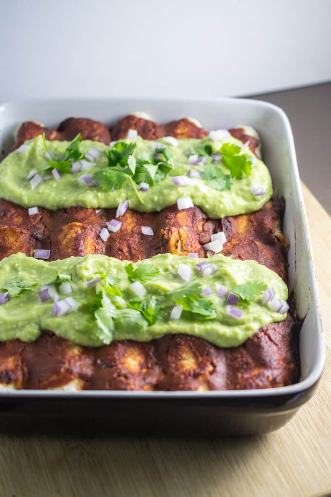 A pan of delicious refined sugar-free breakfast enchiladas with a simple chickpea scramble filling and a tangy and pungent chipotle sauce and cilantro garnish