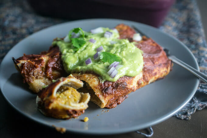 Close up of a gluten, nut, and soy free vegan chickpea scramble breakfast enchilada with a spicy adobo chile chipotle sauce and a rich avocado and lime juice crema