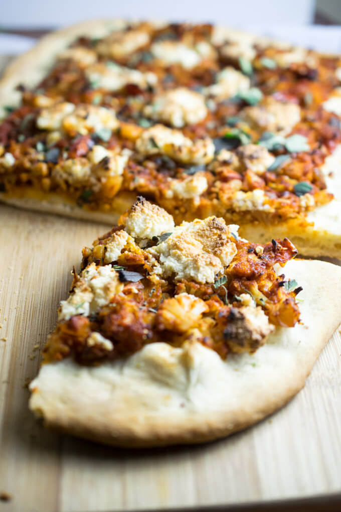 Closeup of one slice of vegan whole wheat pizza with spicy sriracha and tomato sauce, garlic browned cauliflower, salty capers, sweet raisins, and fresh herb toppings