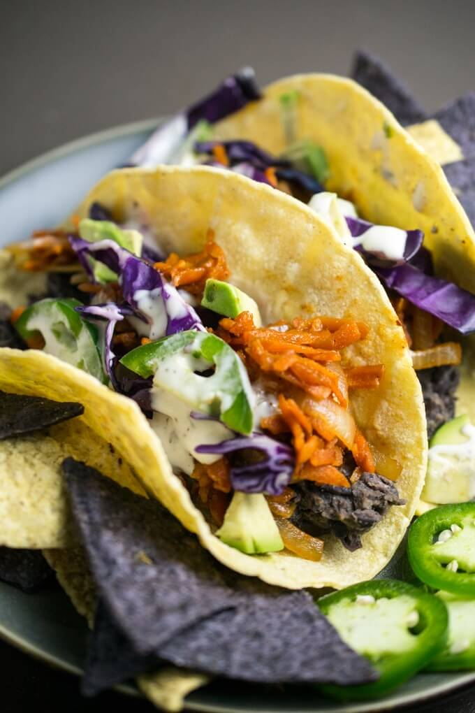 Close up of sweet barbecue pulled carrot tacos served with a creamy ranch dressing, fresh vegetables, spiced black beans, and a side of blue chips