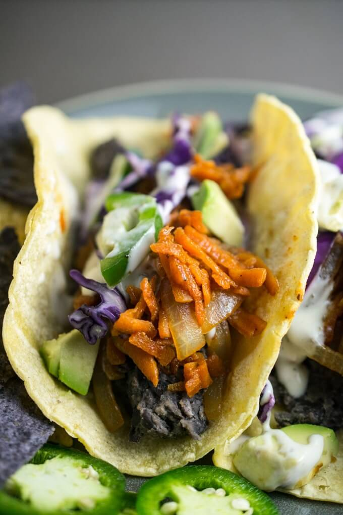 Closeup of saucy and juicy bbq pulled carrot tacos with quick refried beans, spicy jalapeno, crunchy red cabbage, rich avocado chunks, and a crisp tortilla