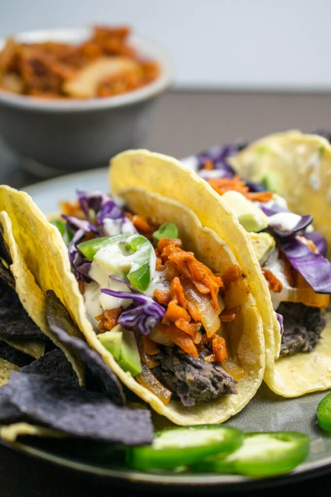 Braised and shredded carrots coated in sweet barbecue sauce paired with yellow onion and black beans, topped with fresh cabbage, rich avocado, and corn tortillas for gluten and nut free vegan tacos | Yup, it's Vegan