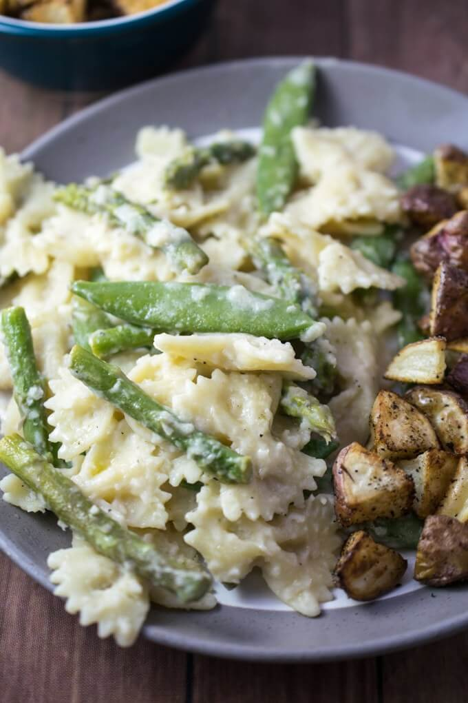 Closeup of creamy white bean sauce coating whole wheat bow tie pasta, and fresh sugar snap peas and asparagus