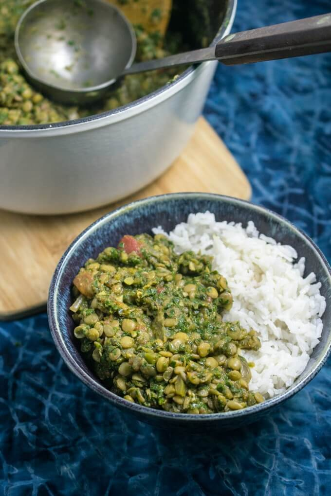 Piping hot, light and tangy spinach lentil curry ladled into a serving dish with the best ever sweet coconut milk rice
