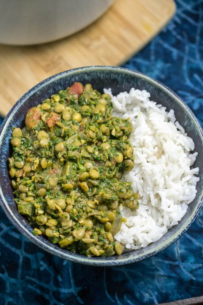 Fluffy jasmine rice cooked in coconut milk for a rich, decadent, slightly sweet flavor spiced with fresh ginger and chili pepper for a kick! Served with a simple lentil spinach curry in a blue bowl