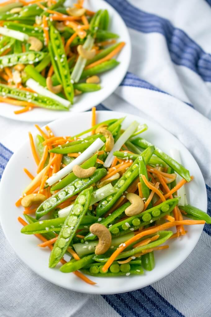 Cashew Sesame Snap Pea Salad | Yup, it's Vegan. This colorful and simple salad is the perfect way to highlight spring veggies. Crunchy snap peas, carrots, cashews, and citrus dressing.