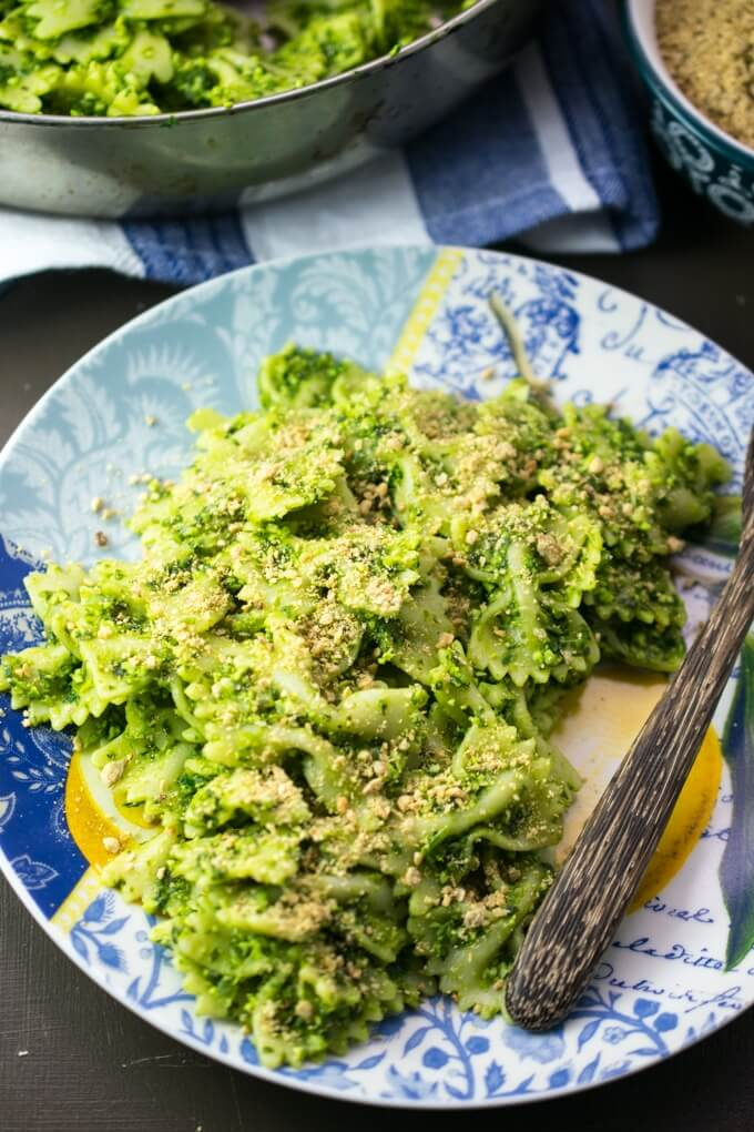 A helping of bowtie pasta with green edamame pesto sprinkled with dairy-free vegan parmesan cheese topping