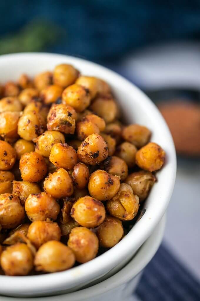 Close-up image of charred, blackened chickpeas with crisped skins, sprinkled with Creole spice, against a blue background.