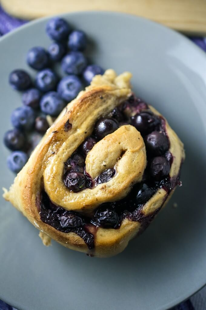 One dairy-free blueberry sweet roll on a gray plate accompanied by fresh blueberries with a cutting board.