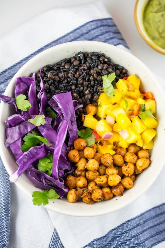 Overhead view of a bowl with equal amounts of yellow mango salsa, black quinoa with lentils, sliced purple cabbage, browned chickpeas, and garnished with fresh coriander.