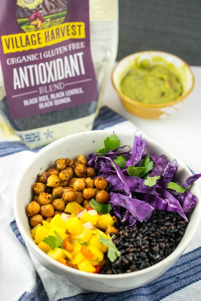 Burrito bowls with pan-fried chickpeas, mango salsa, chopped red cabbage, and black lentils next to a bag of Village Harvest Organic Antioxidant Blend.