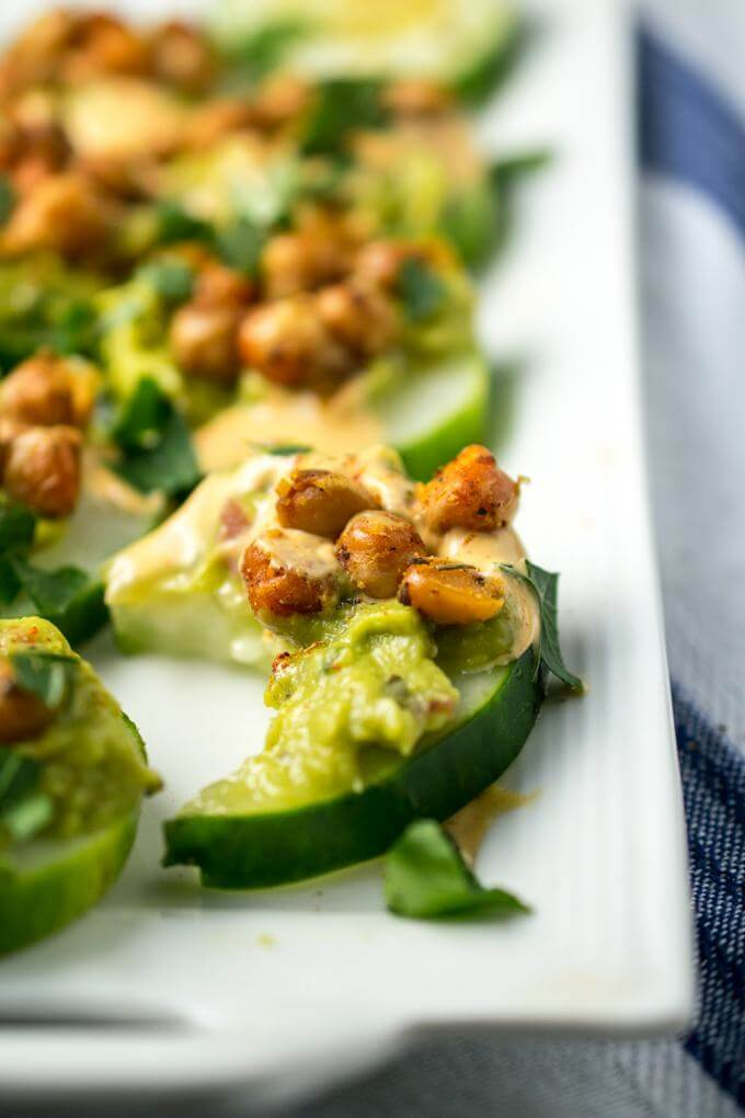 Close-up of one spicy chickpea avocado cucumber bite, with a bite taken out of it and other cucumber slices in the background.