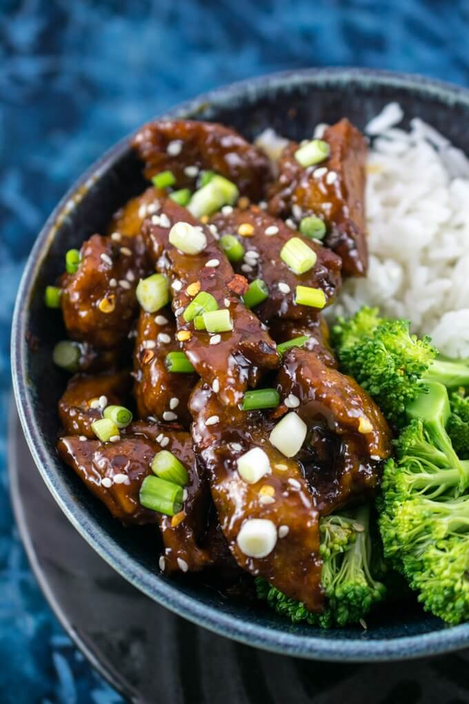 Homemade seitan strips in a sweet and savory soy sauce glaze, with scallions, broccoli, sesame seeds, and a blue patterned background