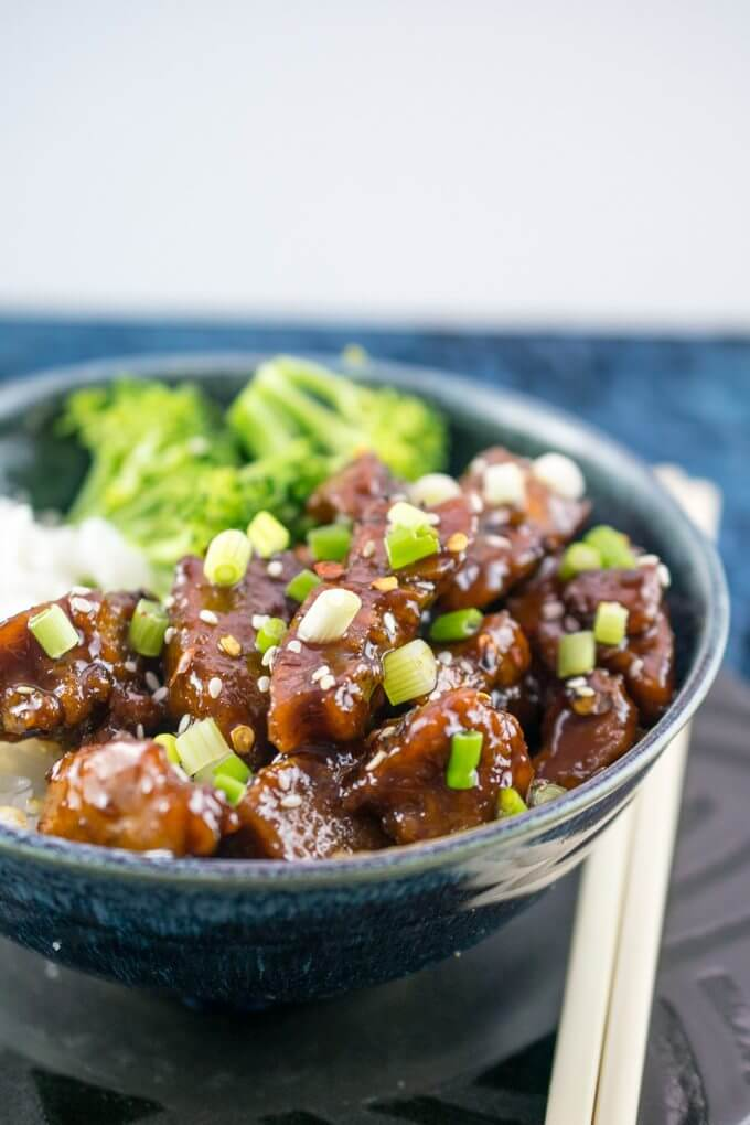 Mongolian Seitan (Vegan Mongolian Beef) | Pan-fried seitan coated in a sweet and spicy, garlic and ginger-infused sauce, served with vegetables and rice, seen here with chopsticks.
