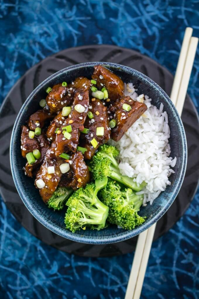 Overhead view of a blue bowl filled with vegan Mongolian beef, steamed broccoli, white jasmine rice, on a black plate next to chopsticks.
