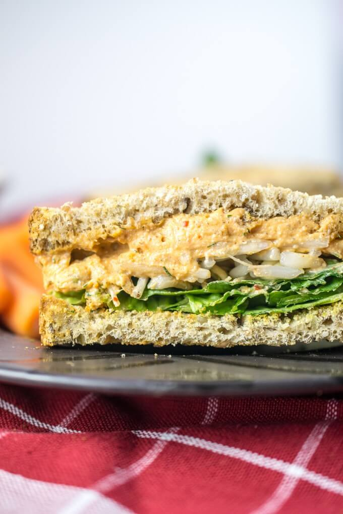 Close-up of a sandwich made with vegan pimento cheese spread, lettuce, and sprouts.