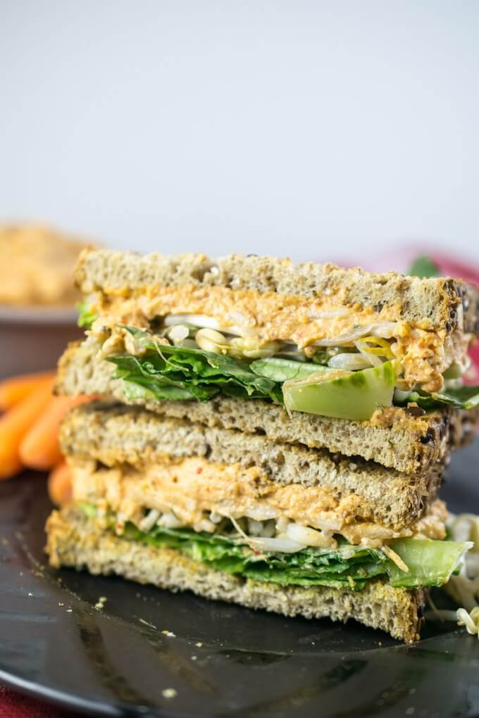 Vegan pimento cheese sandwiches with romaine lettuce, bean sprouts, baby carrots, and a bowl of extra pimento spread in the background.