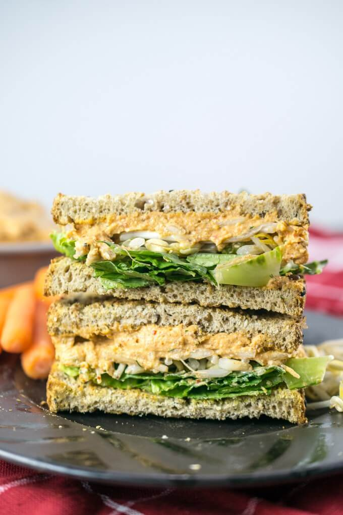 Two stacked sandwich halves of whole wheat bread with orange vegan pimento cheese spread, chopped green lettuce, and bean sprouts, on a black plate with carrots and a red napkin.