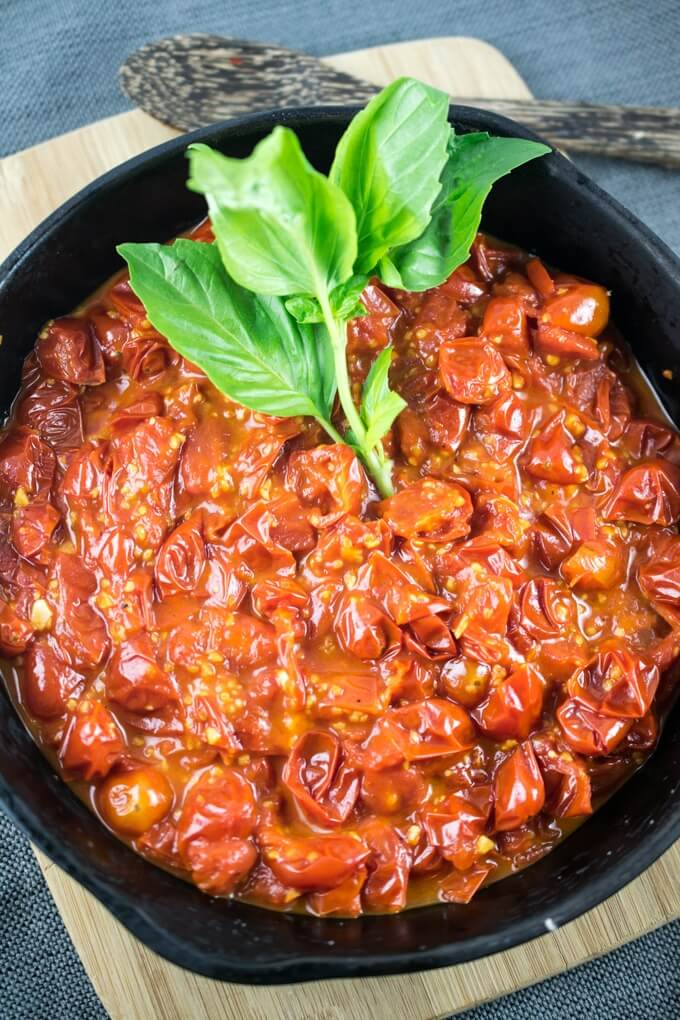 Overhead view of cooked burst cherry tomato sauce garnished with a sprig of basil and a wooden spoon