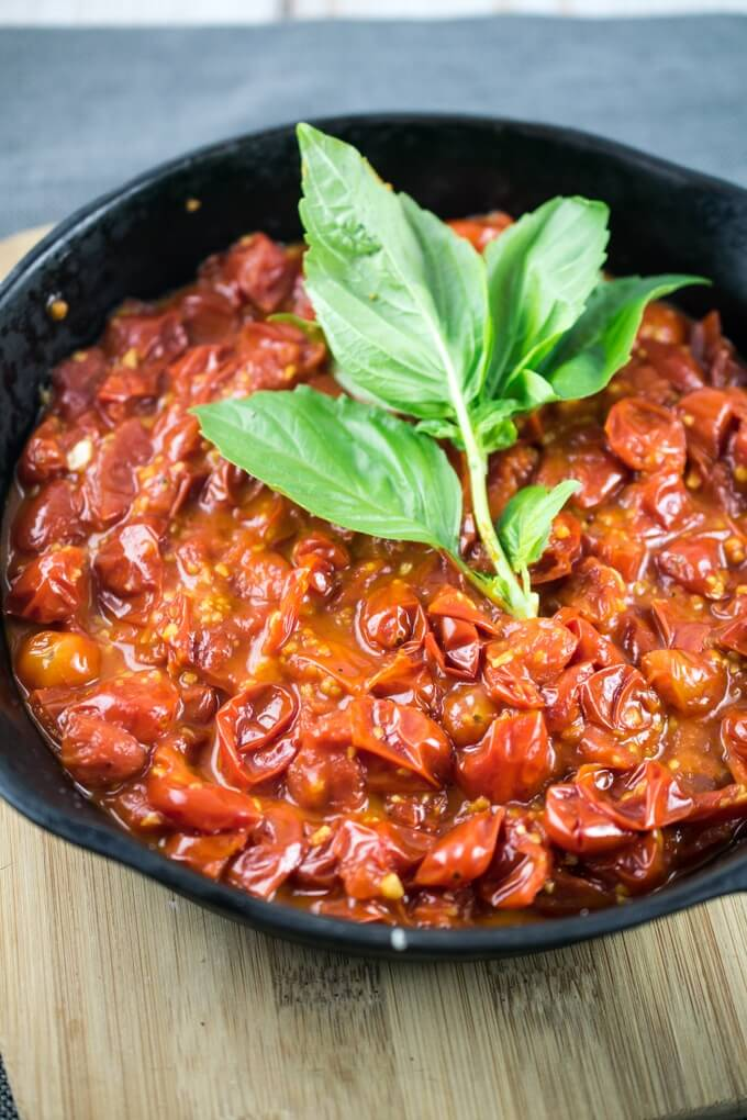 Simple burst cherry tomato sauce simmering in a cast iron skillet with fresh basil and red pepper flakes