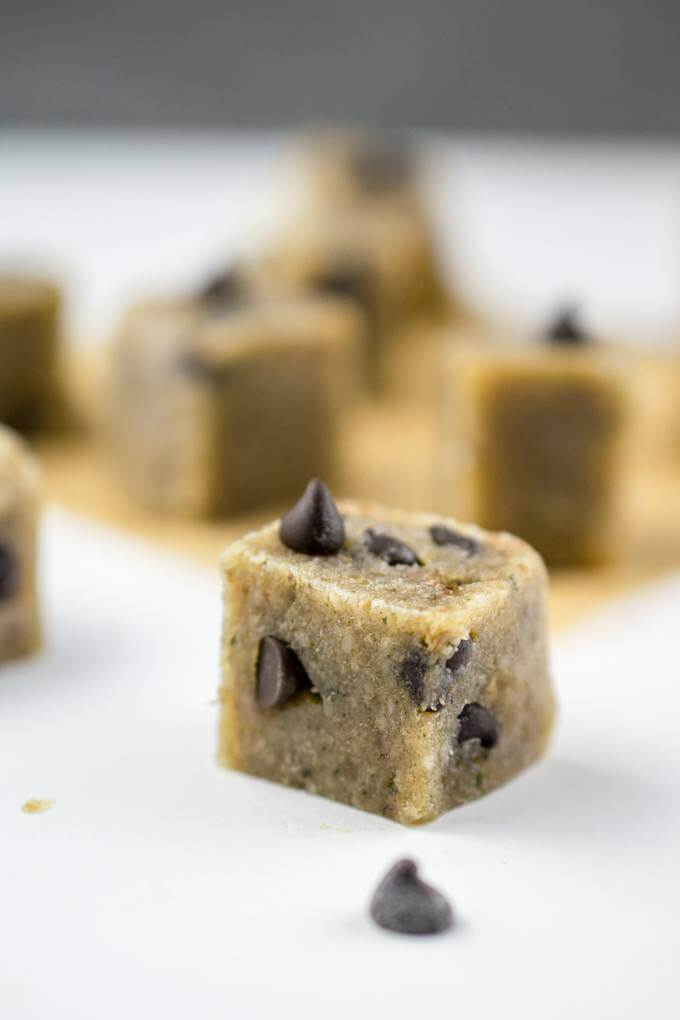 Close-up of a healthy vegan cookie dough square studded with dairy-free chocolate chips. Additional cookie dough fudge squares are in the background.