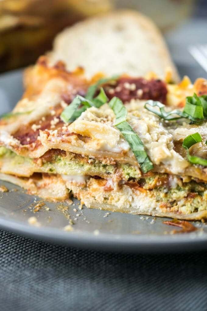 A slice of lasagna on a plate, layered with tofu ricotta, almond pesto, dairy-free cashew mozzarella, tomato sauce and fresh basil.