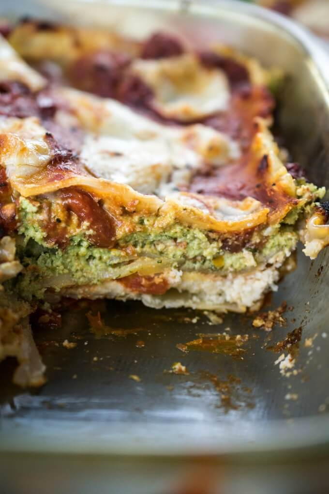 A slice of vegan lasagna inside a glass baking dish, with layers of green and white almond ricotta and tomato sauce.