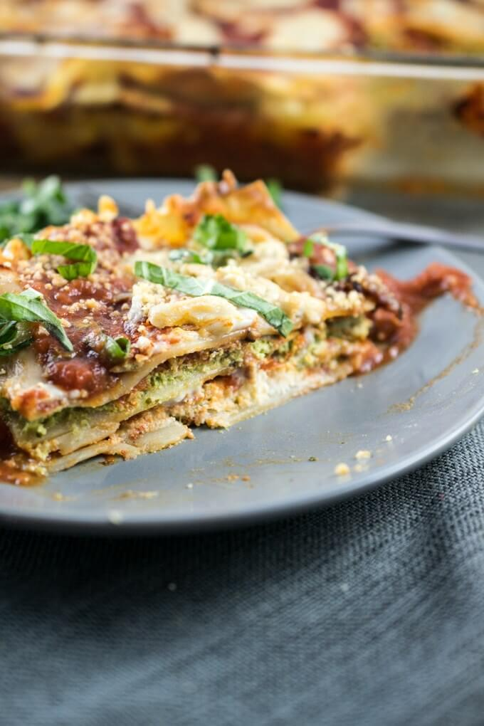 A slice of vegan lasagna on a plate, with the rest of the lasagna in the background. Garnished with fresh basil and gooey cashew mozzarella.