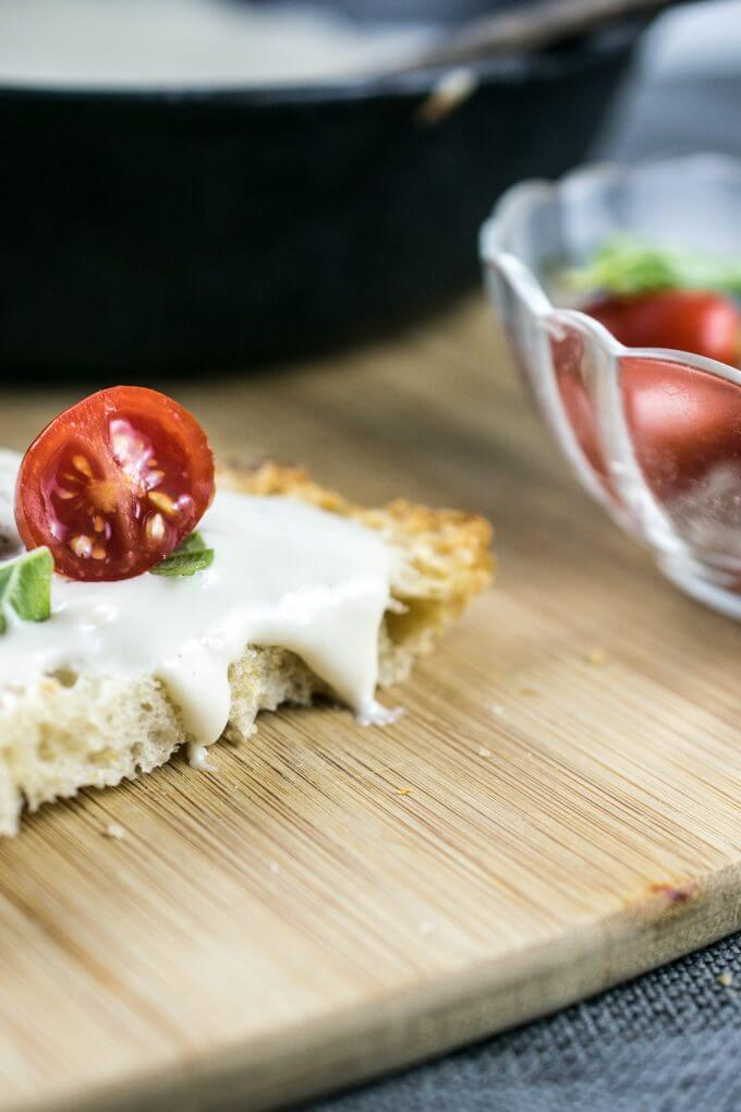 Gooey vegan mozzarella on a slice of bread with sliced tomato and basil.