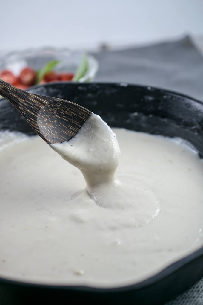 Vegan mozzarella in a cast iron skillet, being stirred with a wooden spoon.