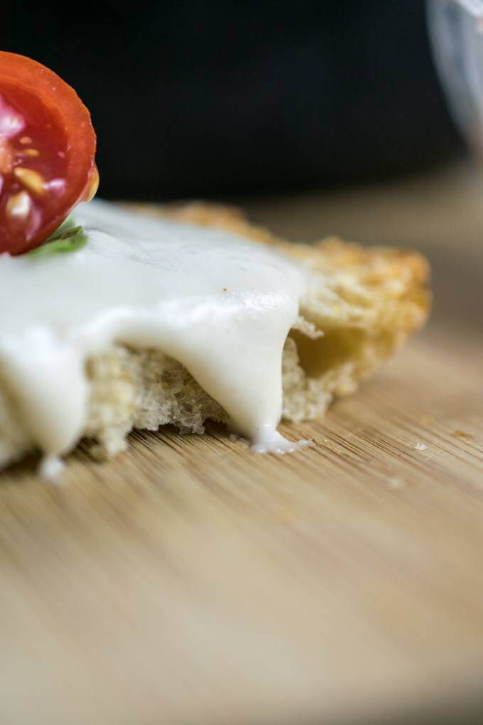 Close-up photograph of stretchy cashew mozzarella dripping off of a slice of bread.