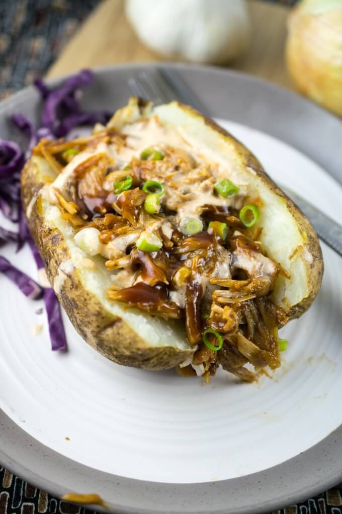 Baked Russet potato on a white plate stuffed with BBQ pulled jackfruit, with purple cabbage, garlic and onion in the background.