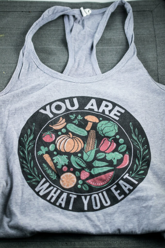 "Grey racerback tank top with the design ""you are what you eat"" and a graphic of an assortment of fruits and vegetables."