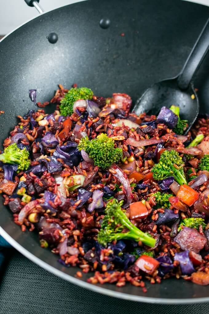 Beetroot, purple cabbage, broccoli, red bell pepper, scallions, rice and sesame seeds being stirred together in a wok.