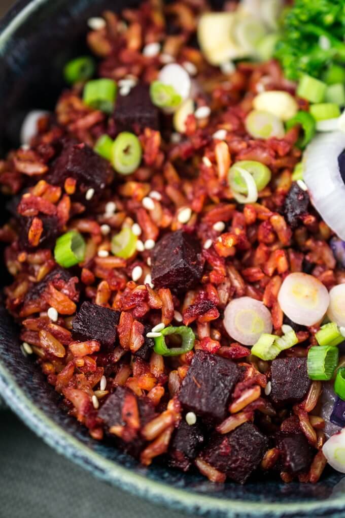 Close-up of diced beetroot coated in coconut oil and spices and being mixed with rice and green onions.