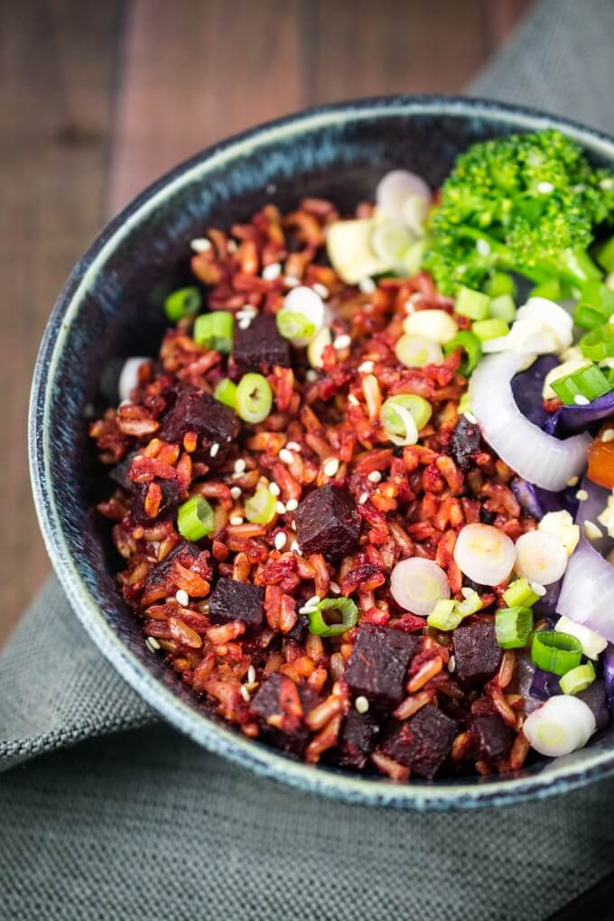 Overhead view of beet fried rice in a blue ceramic bowl with broccoli and sliced onion and scallions. Dark red cubes of beet are mixed into pink hued rice.